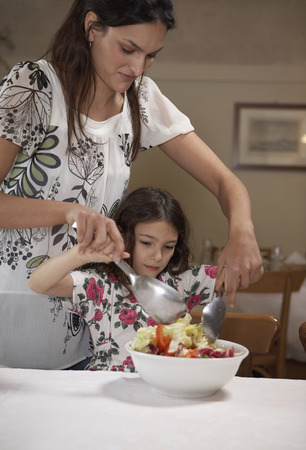 Woman helping daughter (5-7) to toss salad Stock Photo