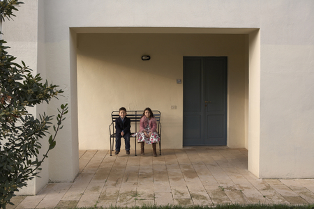 Girl and boy (6-8) sitting on bench outdoors Stock Photo