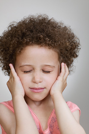 Girl putting her fingers in her ears Stock Photo