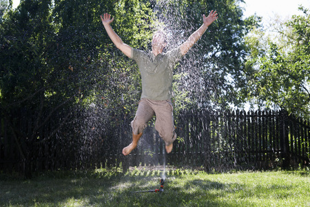 Man jumping through sprinkler.
