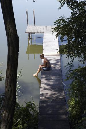 Woman sitting on pier. Фото со стока