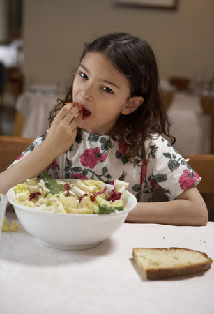 Girl (5-7) eating salad from bowl at a table, portrait