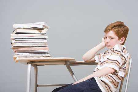 Bored boy sitting at his desk Stock Photo