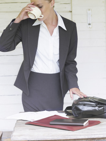 Businesswoman by country cottage Stock Photo