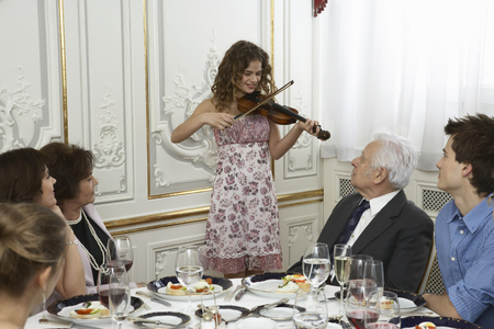 Girl (9-11) playing violin to family around table