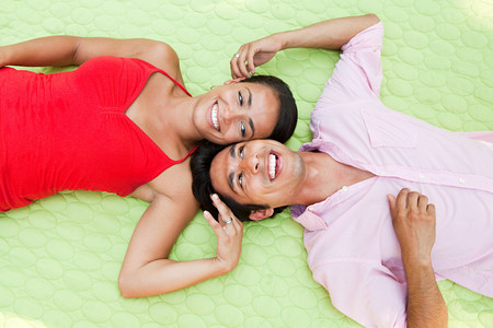 Mid adult couple lying on blanket outdoors, portrait