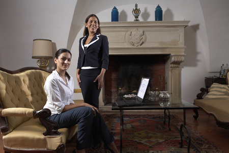 successfulness: Two women with laptop in living room, smiling, portrait