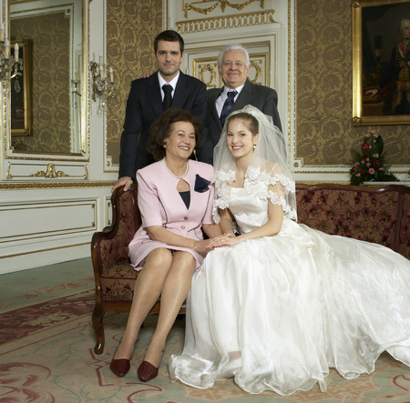 Bride and groom with parents, smiling, portrait