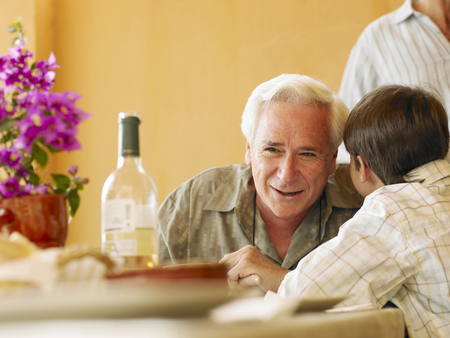 Boy (8-10) whispering in grandfathers ear at dining table