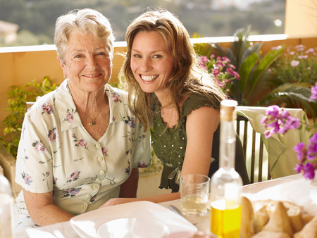 Senior woman and adult daughter sitting at dining table on balcony, portrait Stock Photo