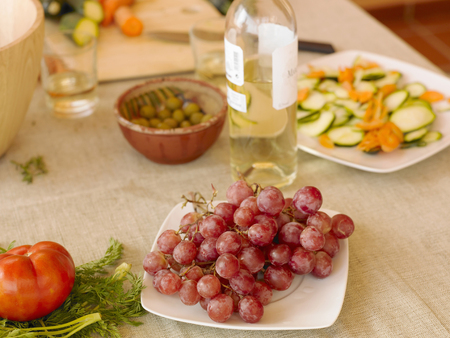 Black grapes, white wine, olives and salad on dining table (still life) Stock Photo