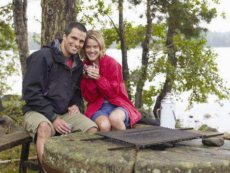 ruck sack: Couple sitting in a park by a fire pit smiling.