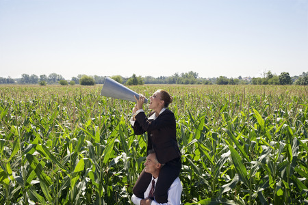 Businesswoman on businessman's shoulders with megaphone.