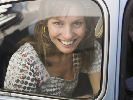 Woman sitting in car, looking through window, smiling, portrait