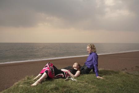 Couple sitting next to a beach Stock Photo