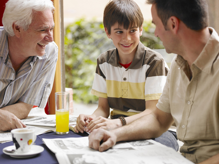 Boy (8-10) sitting in café with father and grandfather, smiling