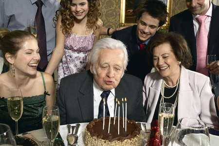 Senior man blowing out candles on cake