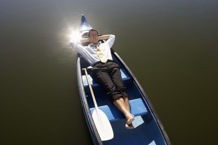Businessman asleep in canoe.