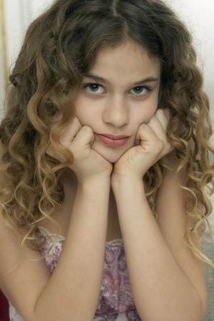 Girl (9-11) leaning with hands on chin, portrait Stock Photo