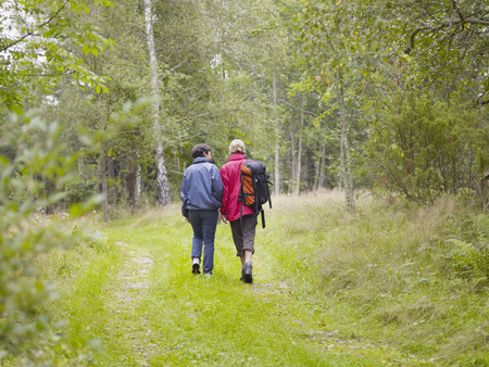 ruck sack: Two women walking through a forest with a backpack smiling.