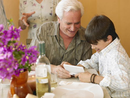 Boy (8-10) and grandfather playing portable video game at dining table Stock Photo