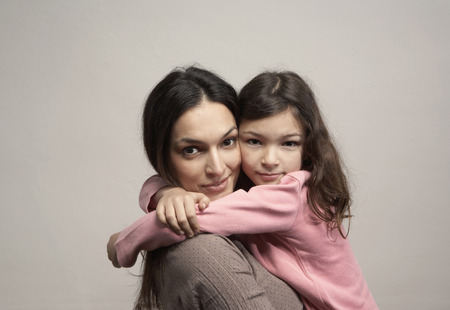 Mother embracing daughter (5-7), portrait