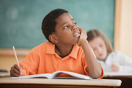 Schoolboy daydreaming in classroom Foto de archivo