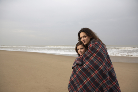 Mother and daughter wrapped in blanket at seaside