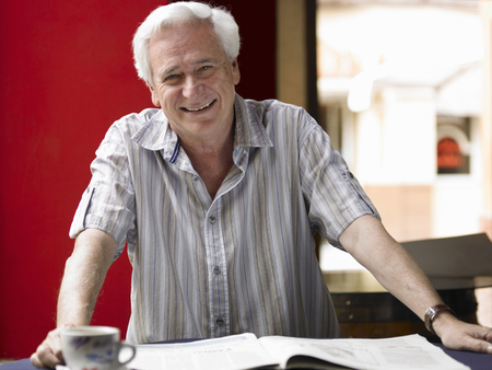 Senior man reading newspaper in café, smiling, portrait Stock Photo - 85954643