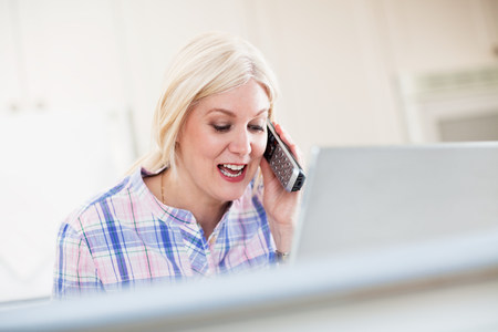 Mature woman taking a phone call from home office