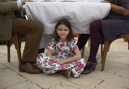Girl (9-11) sitting under family table, portrait