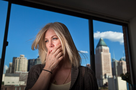 nightmarish: Mature woman looking anxious in office with cityscape visible behind Stock Photo