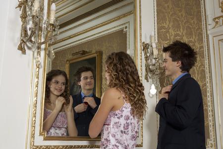 Girl (9-11) and teenage boy (15-17) looking in mirror