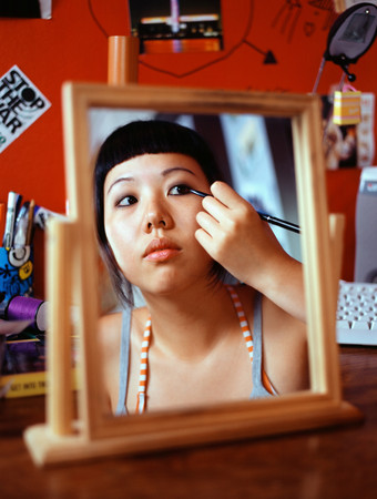 Teenage girl applying eyeliner Stok Fotoğraf - 86037685