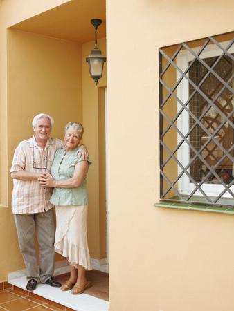 Senior couple standing on front porch, smiling, portrait