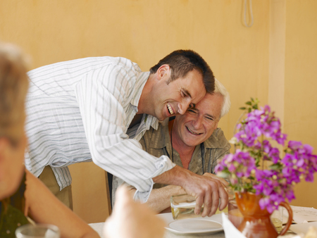 Senior man sitting at dining table on balcony, adult son pouring wine Stock Photo