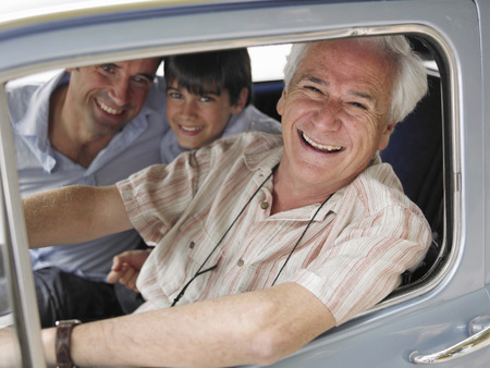 Boy (8-10) sitting in car with father and grandfather, portrait Imagens