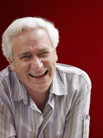 Senior man standing beside red wall, laughing, portrait Stock Photo