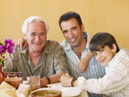 Boy (8-10) sitting at dining table with father and grandfather, smiling, portrait