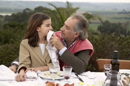 Girl (9-11) sitting with grandfather at a table outside