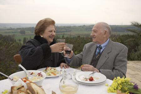 Senior couple toasting outdoors Stock Photo