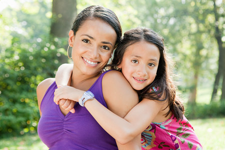 Mother and daughter smiling in park, portrait