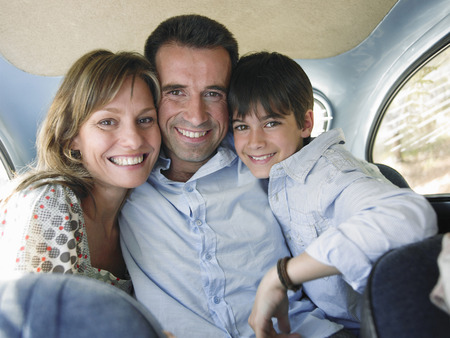 Family sitting in backseat of car, smiling, portrait Stock Photo