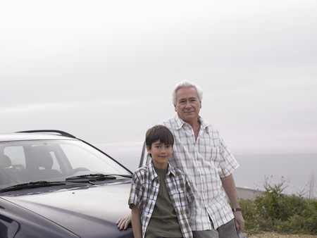 Boy (8-10) and grandfather standing beside car at beach, smiling, portrait