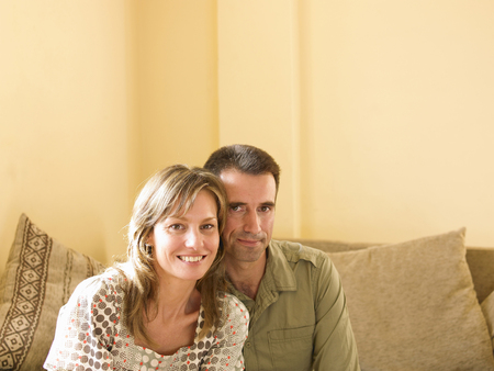 Couple sitting on sofa at home, smiling, portrait