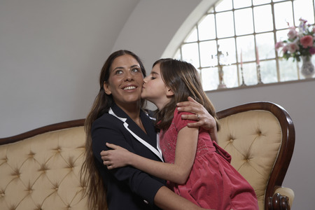 Daughter (9-11) kissing mother on sofa