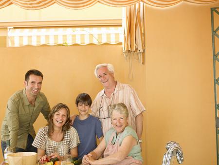 Familia multigeneracional preparando comida en casa, sonriente, retrato Foto de archivo