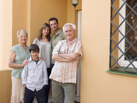 Multi-generational family standing on front porch, smiling, portrait Stock Photo