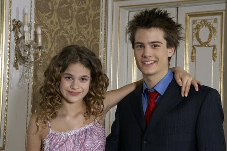 Girl (9-11) and teenage boy (15-17) smiling, portrait