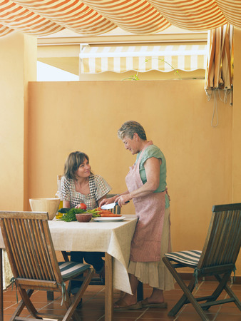 Senior woman preparing food at home, adult daughter looking on Stock Photo